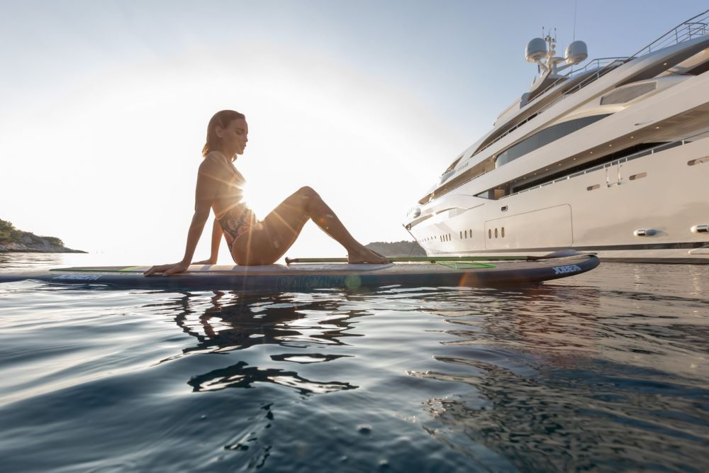 Woman paddleboarding from a Superyacht