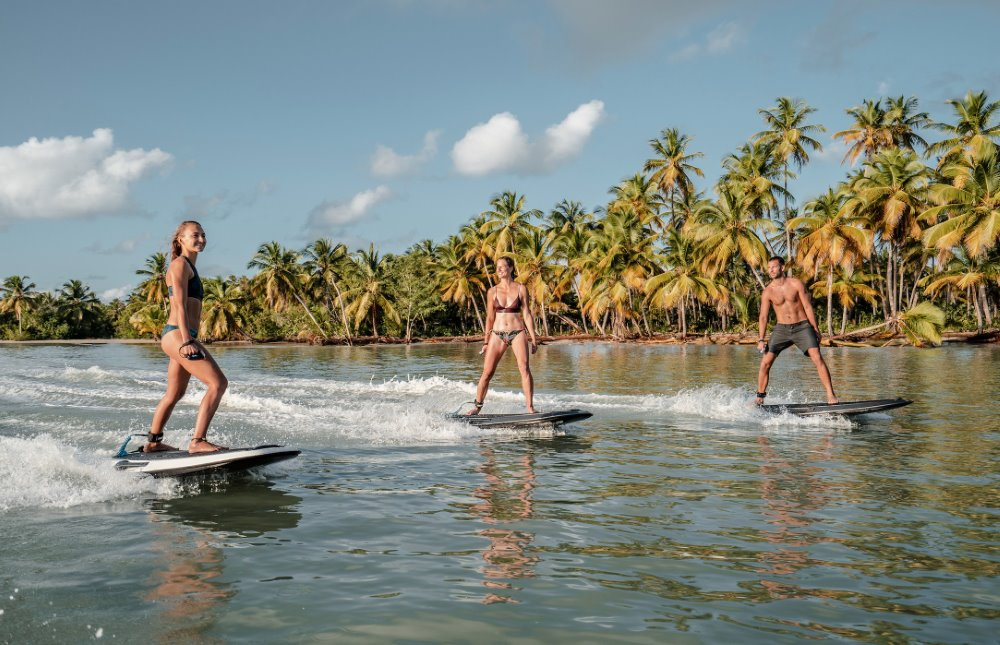 Three people surfing on powered boards from a superyacht