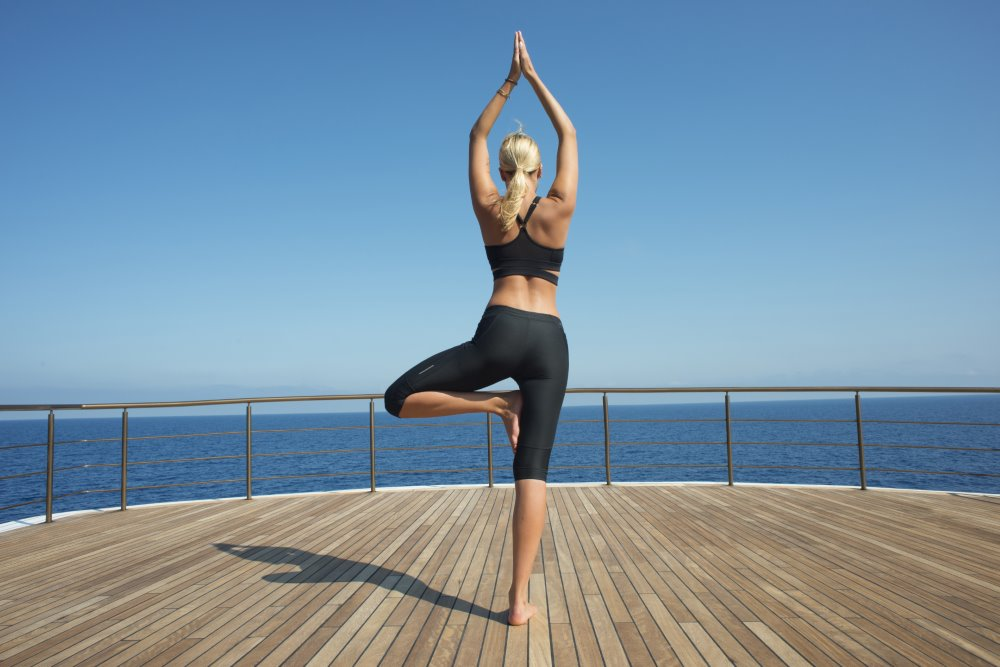 Woman practicing yoga on a superyacht