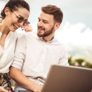 Beautiful romantic couple using laptop. Watching pictures on the laptop