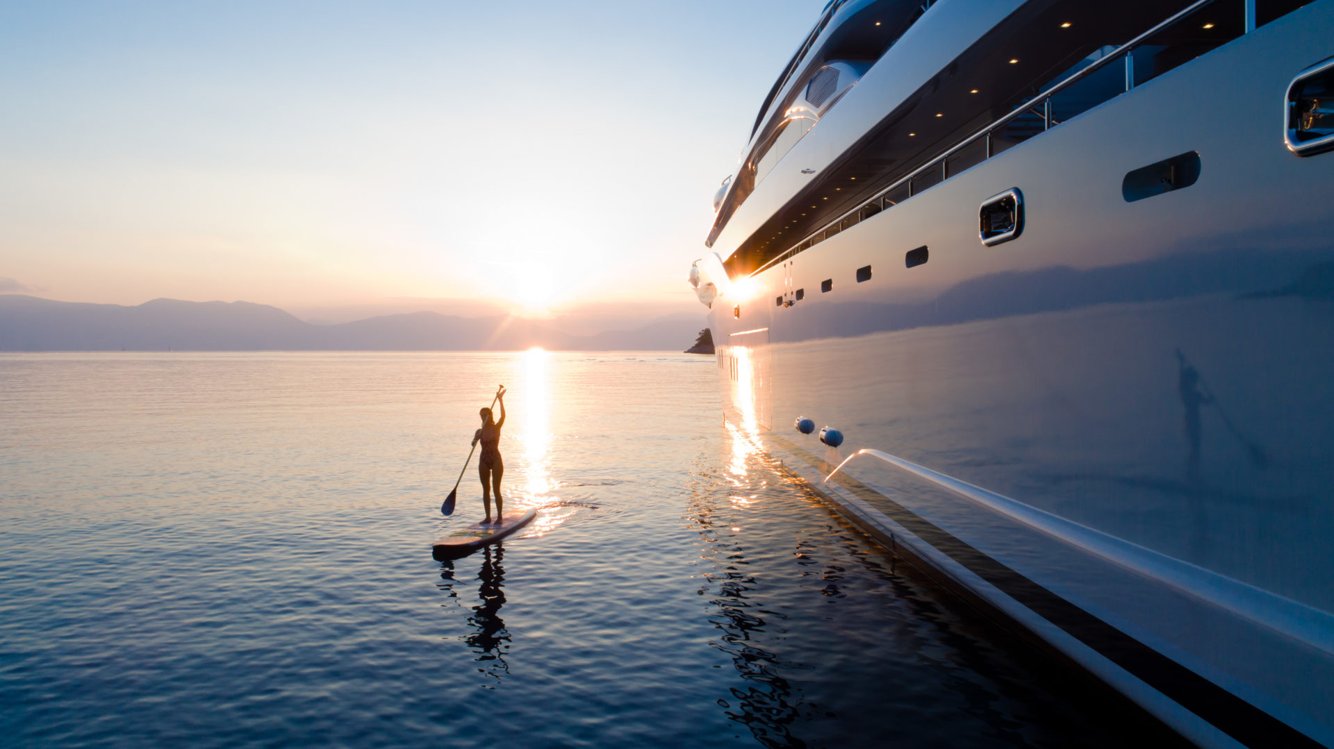 Yacht and woman on paddle board